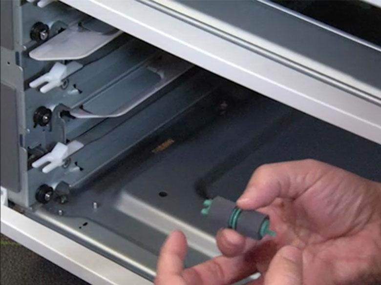 Retirar los rodillos de carga de papel de los ejes