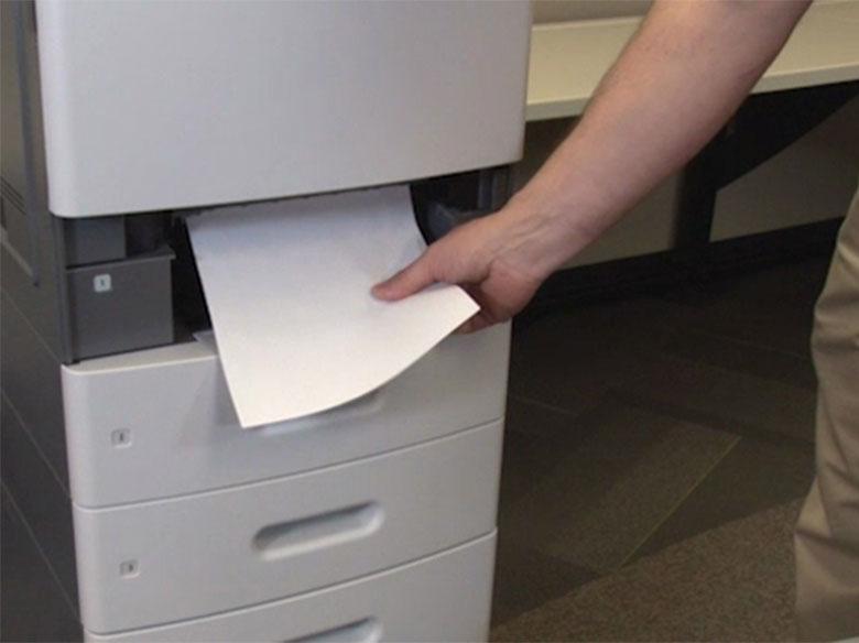 Extraiga la bandeja completamente y, a continuación, retire el papel atascado