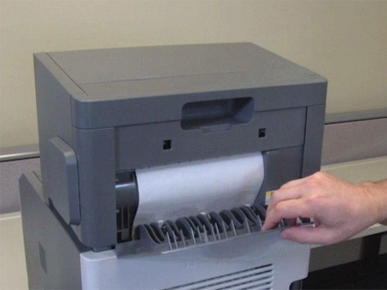 Extraer el papel atascado de la parte posterior de la impresora