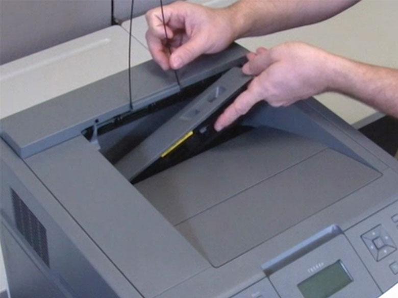 Soulever le presse-papier, puis réinstaller le capot de la raclette de l'unité de fusion.