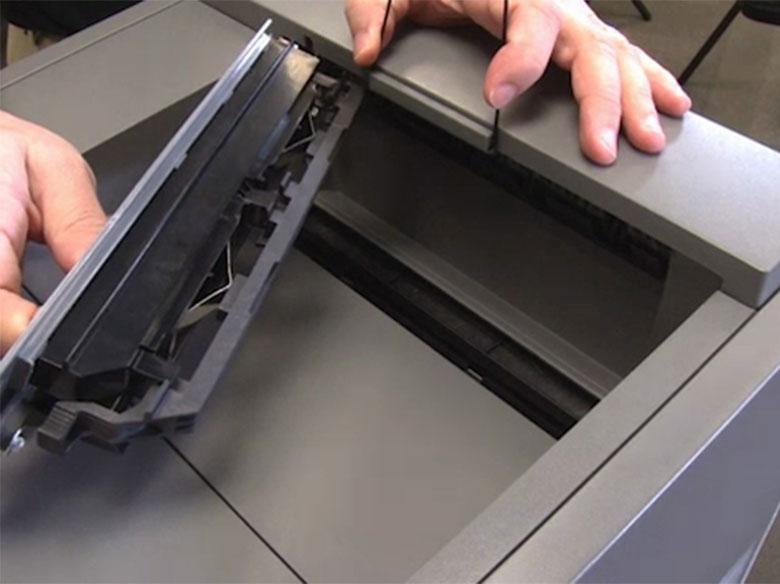 Soulever le presse-papier, puis retirer le capot de la raclette de l'unité de fusion